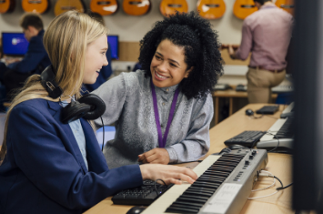 Teacher helping a student at the keyboard