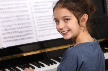 A girl smiling at the piano